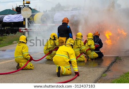 Team Thailand firefighters extinguished the blaze, flames, smoke close to the train tanker, which is dangerous. - stock photo