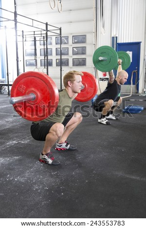 Team trains squats at fitness gym center - stock photo