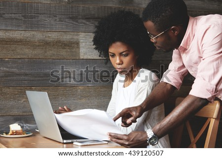 Team work: two corporate workers in casual wear discussing new project. African man in glasses holding papers showing a report to his African female colleague, who is listening to him attentively - stock photo