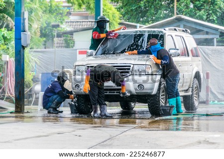 team Worker washing car in the carwash - stock photo