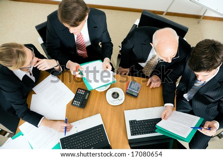 Team (young people and a senior figure) working hard, discussing contractual documents - stock photo