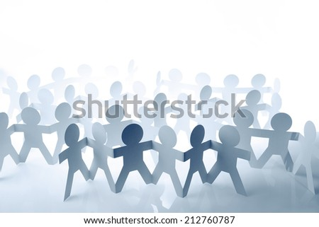 Teams of paper doll people holding hands - stock photo