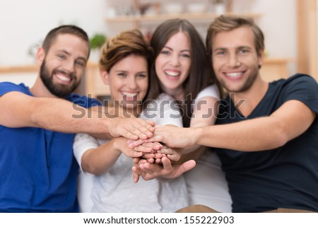 Teamwork amongst friends with a laughing enthusiastic group of young people stacking their hands together with focus to the hands - stock photo