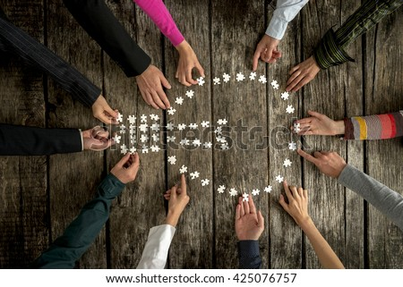 Teamwork and cooperation concept - group of twelve people, male and female, assembling a light bulb shape with blank puzzle pieces on a rustic textured desk, top view. - stock photo