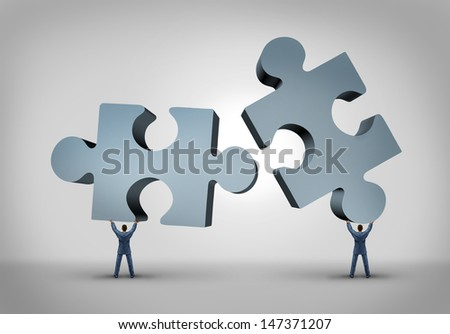 Teamwork and leadership business concept as two giant three dimensional puzzle pieces coming together from a partnership agreement between two powerful leaders who are building a successful company. - stock photo