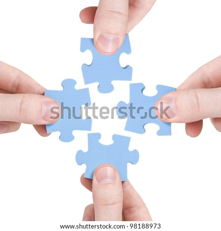 teamwork and partnership  concept. four hands connecting  puzzle - stock photo