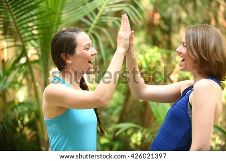 Teamwork and two friends giving a high five - stock photo