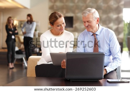 Teamwork at office. Portrait of  businesswoman holding digital tablet while consulting with senior manager. Team sitting at business meeting in front of laptop. Business persons at background.  - stock photo