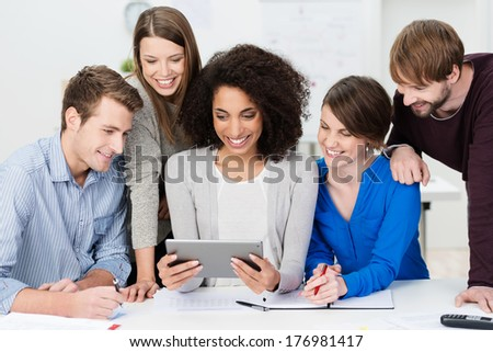 Teamwork at the office with a group of enthusiastic smiling young business people clustered around a pretty African American woman holding a tablet computer - stock photo