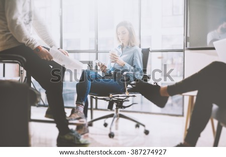 Teamwork concept, brainstorming. Businessman crew working with new startup project in modern loft. Woman holding smartphone hands. Horizontal, film effect - stock photo
