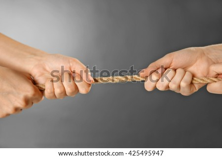 Teamwork concept. People hands pulling the rope on grey background - stock photo