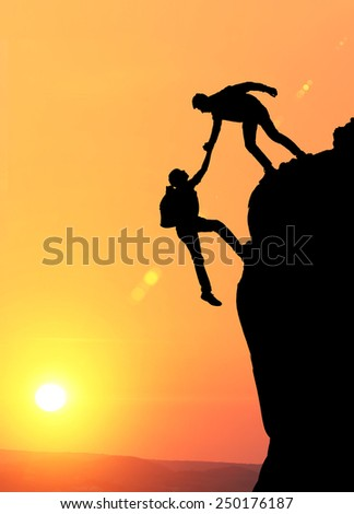 Teamwork couple hiking help each other trust assistance silhouette in mountains, sunset. Teamwork of two men hiker helping each other on top of mountain climbing team, beautiful sunset landscape. - stock photo