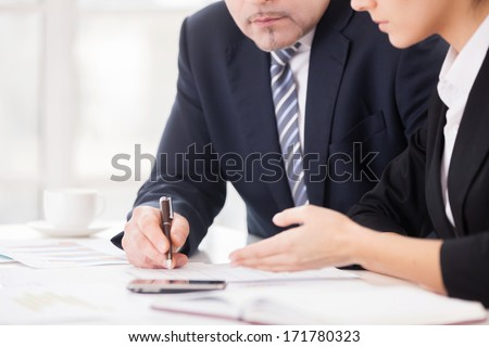 Teamwork. Cropped image of two confident business people discussing something while sitting together at the table - stock photo
