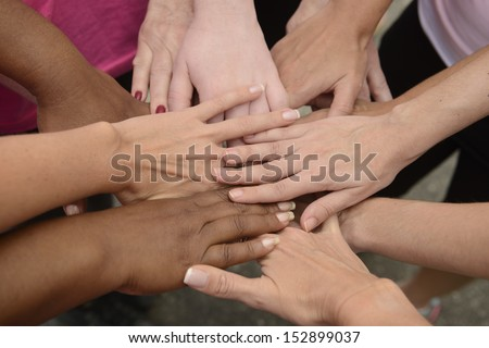 Teamwork: group putting hands together  - stock photo