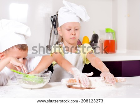 Teamwork in the kitchen as a cute little boy and girl in chefs uniforms learning to bake roll out the dough and get flour ready to sprinkle on top - stock photo
