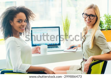 Teamwork makes great work. Two cheerful young women looking at camera and smiling while sitting at working place  - stock photo