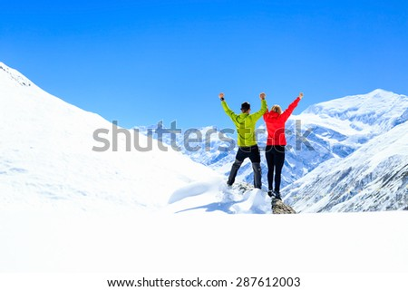 Teamwork motivation, couple hikers climbers with arms up, fitness and sport woman success in winter mountains. Inspiration beautiful landscape and healthy lifestyle on snow in Himalayas, Nepal. - stock photo