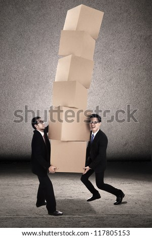 Teamwork photo concept: Two businessmen trying to balance plenty of boxes together - stock photo