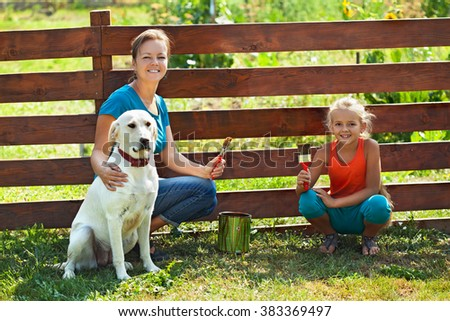 Teamwork - woman with little girl and dog painting a fence in summer time - stock photo