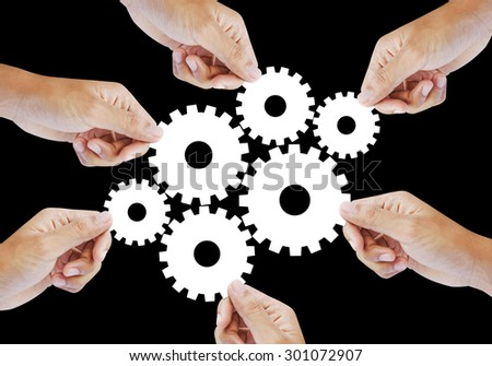 Teamwork works together to build a cog wheel gear system, Business concept. - stock photo