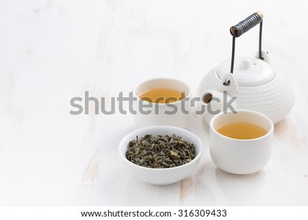 teapot and cups of green tea on a white wooden background, horizontal - stock photo