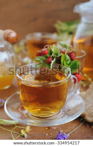 Teapot and cups of herbal tea with herbal flowers and strawberries on wooden table - stock photo