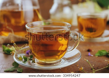 Teapot and cups of herbal tea with  linden flowers and lavender on wooden table - stock photo