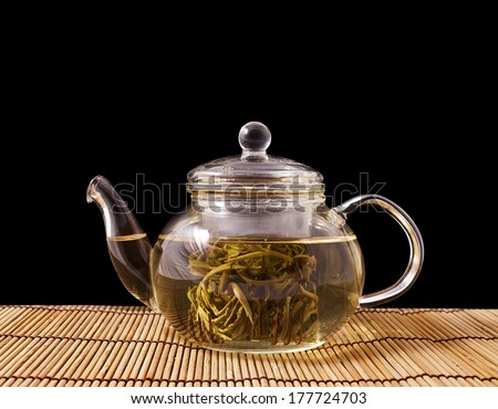 Teapot and glass cups with the chinese jasmine tea Mo Li Long Zhu(Jasmine Pearls) isolated on black background  - stock photo