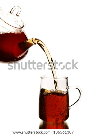 Teapot and tea glass with black tea, isolated on white - stock photo
