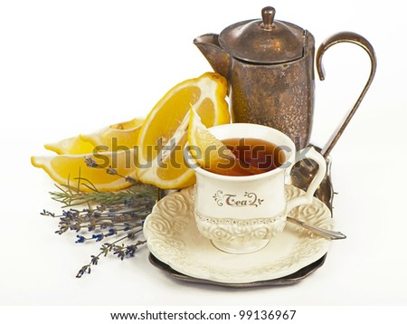 Teapot and tea in cup and lemon isolated on white background - stock photo
