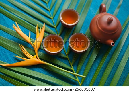 Teapot and three teacups, coil of rope, green leaves and yellow flower on blue wooden background. - stock photo