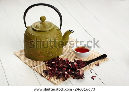 teapot, bowl and tea on wooden table - stock photo