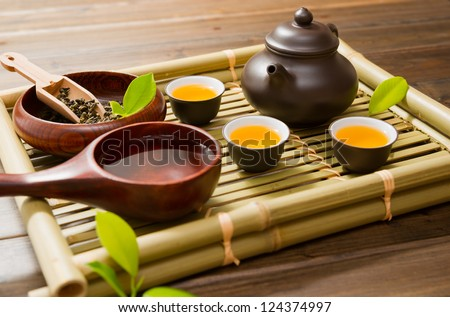 teapot,tea cup and tea leaves on a bamboo mat - stock photo