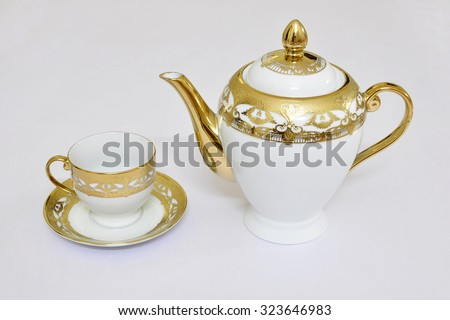 Teapot with cup and saucer on a white background. - stock photo