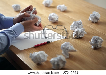 Tearing up another crumpled paper ball for the pile - stock photo