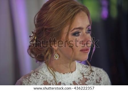 Tears pour down bride's cheek while she looks far away - stock photo