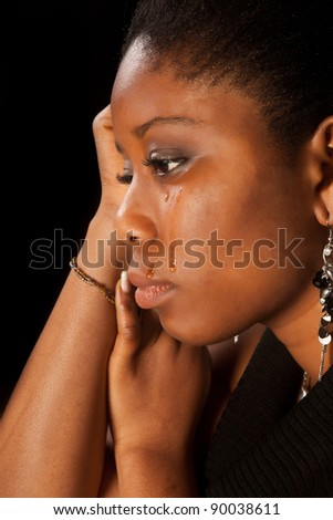 Tears running of the face of a young african woman - stock photo