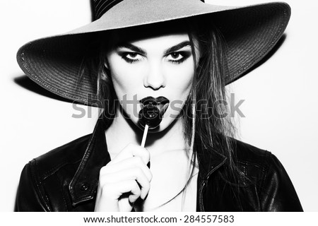 Teasing young blonde woman black and white portrait with bright make up in hat and leather jacket looking forward holding and licking round sugar candy standing on light background copyspace - stock photo