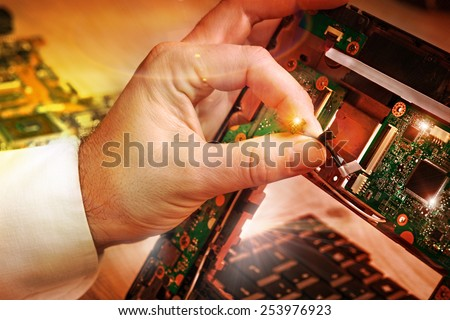 Tech fixes laptop motherboard in service center. Shallow DOF, focus on hand, image is toned with extra light effects  - stock photo