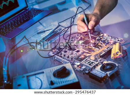 Tech fixes motherboard in service center. Shallow DOF, focus on hand, image is toned with extra light effects  - stock photo