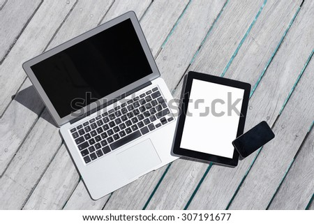 Tech gadgets on wooden deck - stock photo