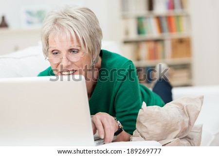 Tech savvy senior woman relaxing with a laptop at home lying on a sofa wearing her glasses and reading the screen - stock photo