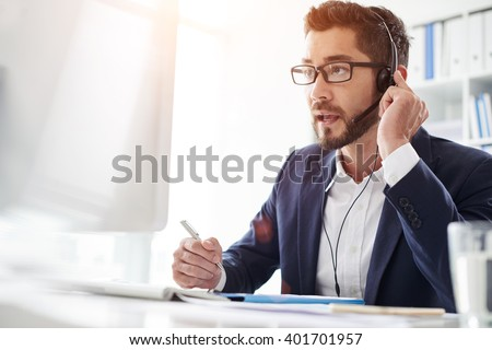 Tech support manager in headset consulting a client - stock photo