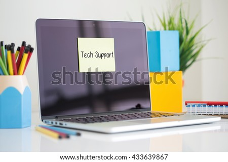 Tech Support sticky note pasted on the laptop - stock photo
