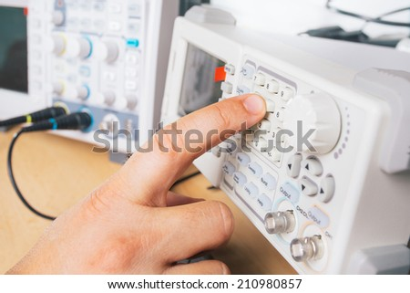Tech tests electronic equipment in service - stock photo