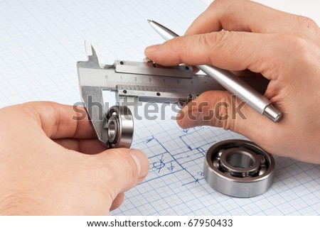 Technical drawing and callipers with bearing in hand on graph paper - stock photo