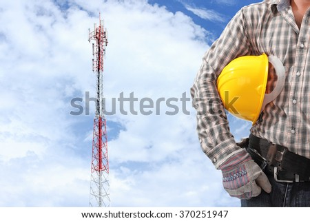 technician against telecommunication tower painted white and red used to transmit telephone mobile signals - stock photo