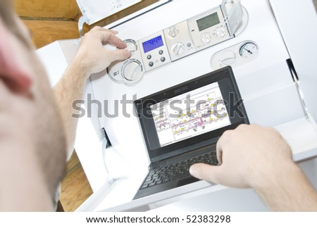 Technician at work. Servicing water & heating systems - stock photo