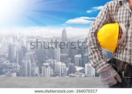 technician holding helmet working at high building construction site against blue sky with in concept ecology and real estate - stock photo