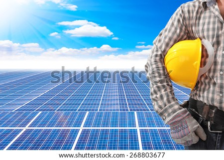 technician holding helmet working at solar energy power plant against beautiful sky with in concept ecology  - stock photo